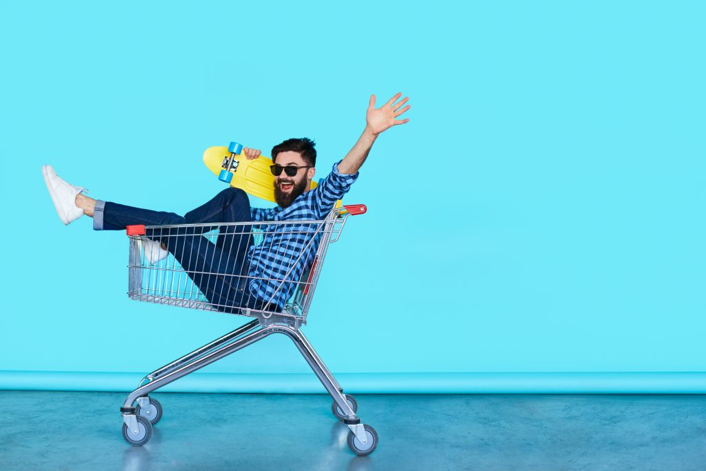 Carefree hipster fun. Side view of cheerful young man sitting in shopping cart with skateboard over blue wall with copy space.